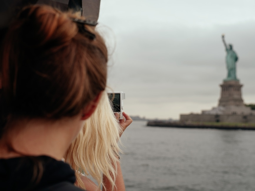 Woman Blonde Hair Taking Picture of Statue of Liberty