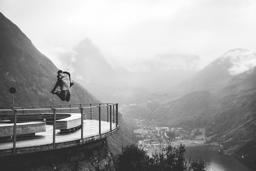 Greyscale Photo of Man Jumping Near Metal Rail and Mountain at Daytime