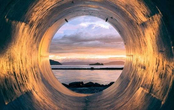 Blue Ocean Water during Sunset Through Round Hole
