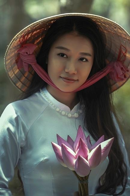 Mujer que desgasta la camisa blanca de manga larga y Sakkat sombrero que sostiene las flores rosadas