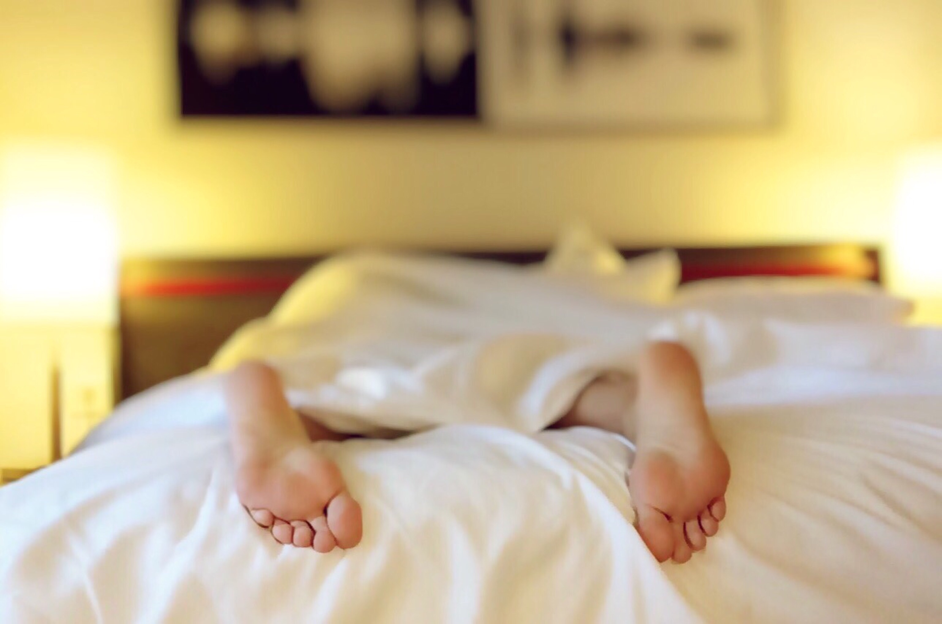 Image of a person sleeping with their feet in the foreground and the rest of their body covered in a blanket