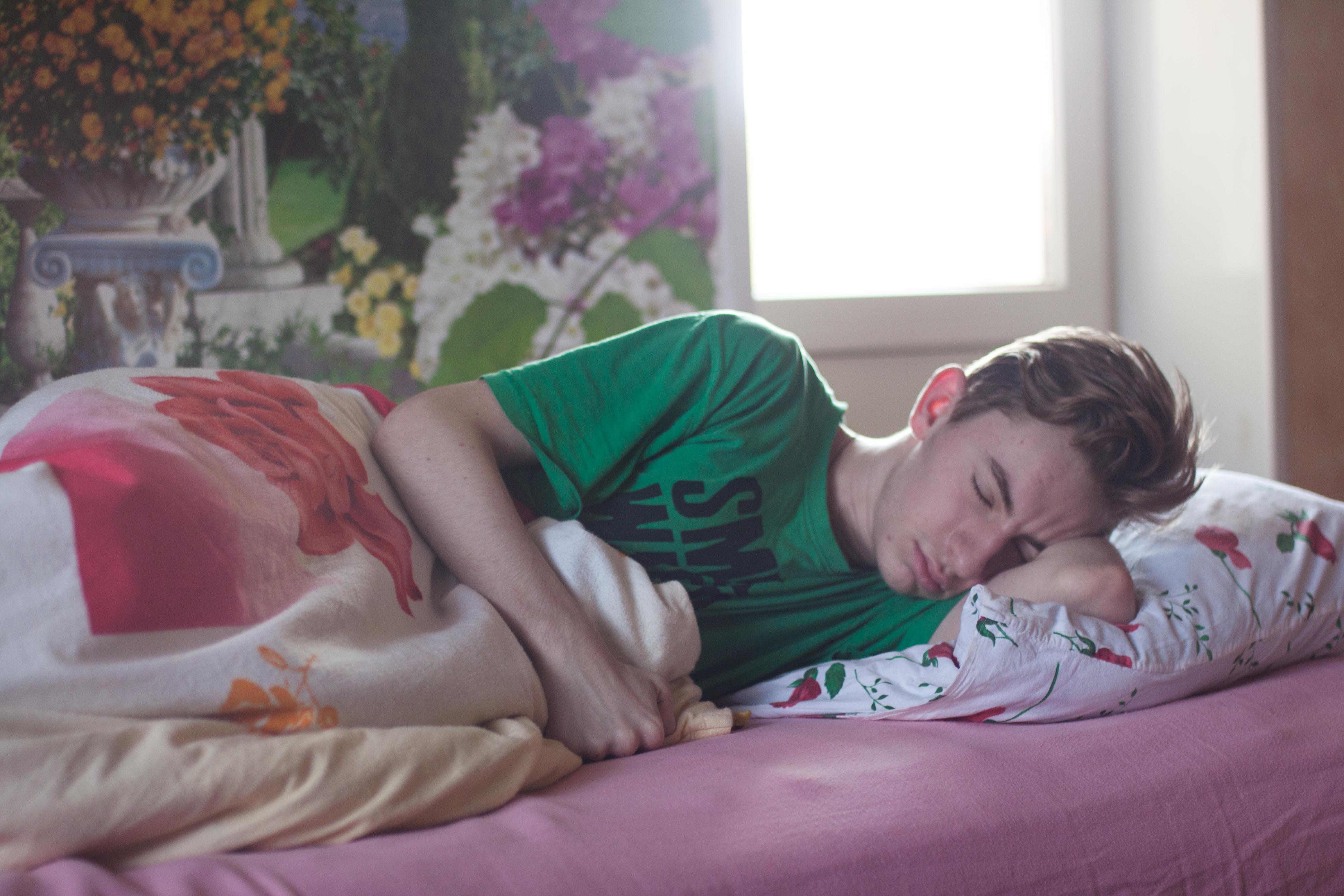 Boy lying sideways on a bed sleeping.