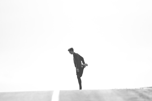 Person Standing on One Leg Black and White Photo