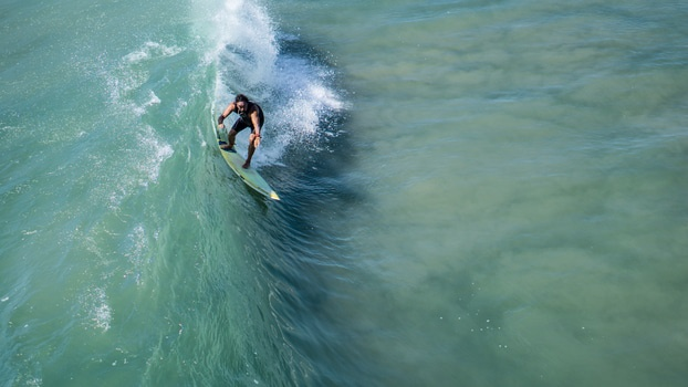 Man Surfing on Green Water