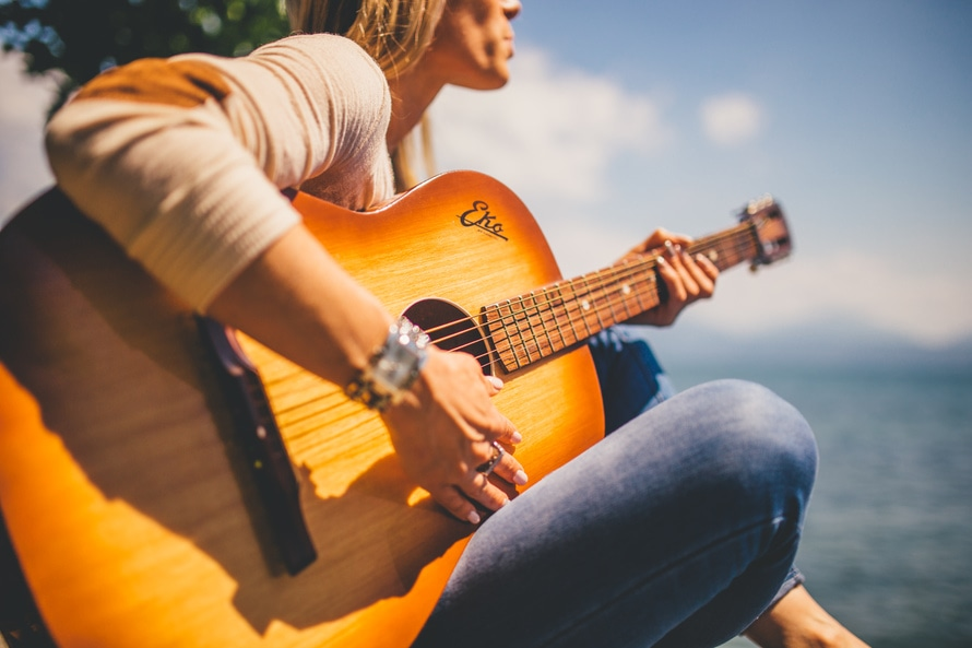 Woman Sitting Holding Guitar