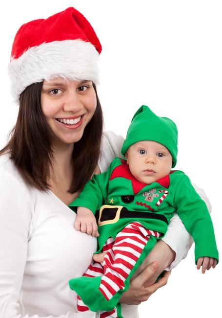 Mujer sonriente con el sombrero de Santa Carring bebé vestir traje de Elf