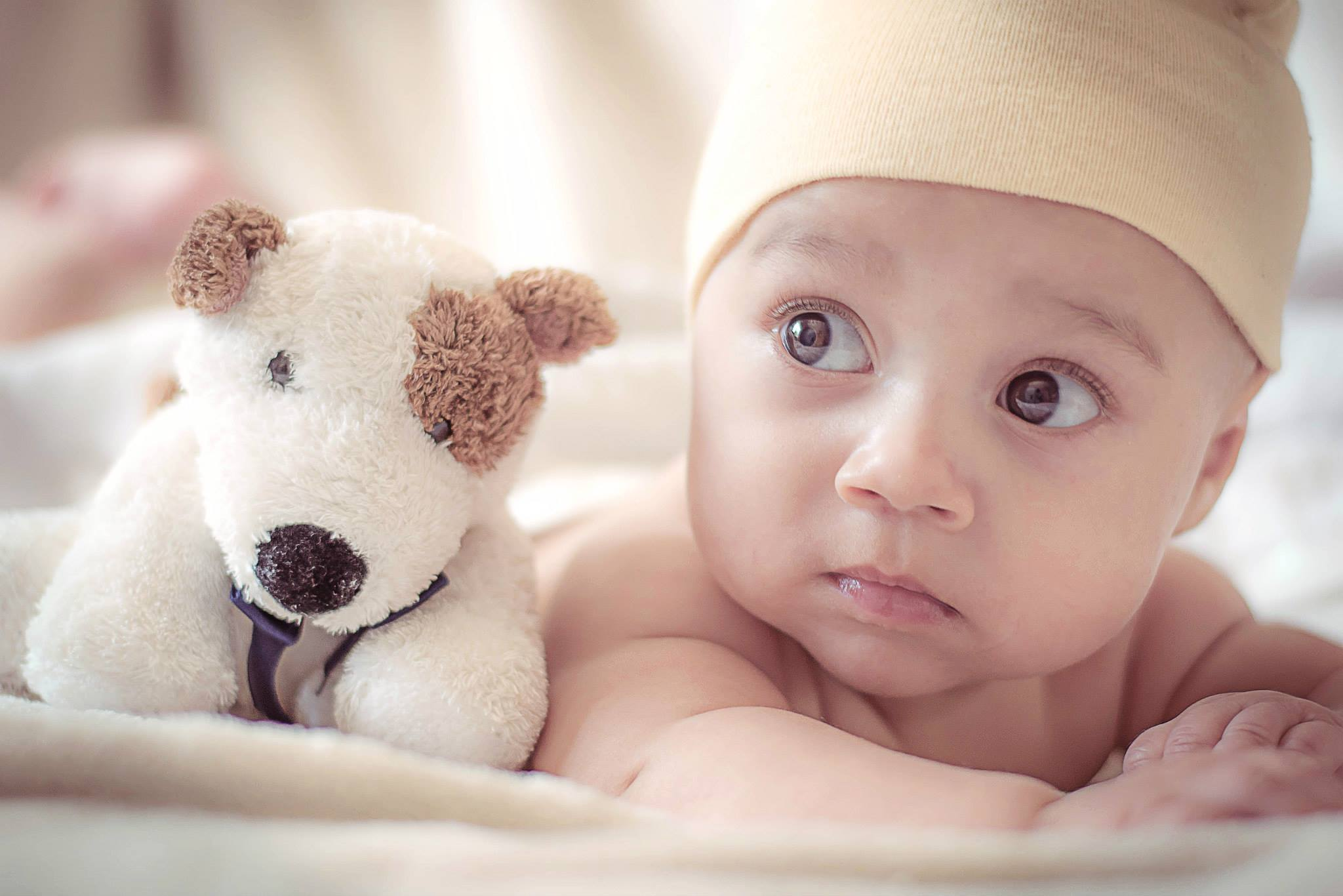 A baby lies next to a stuffed toy.
