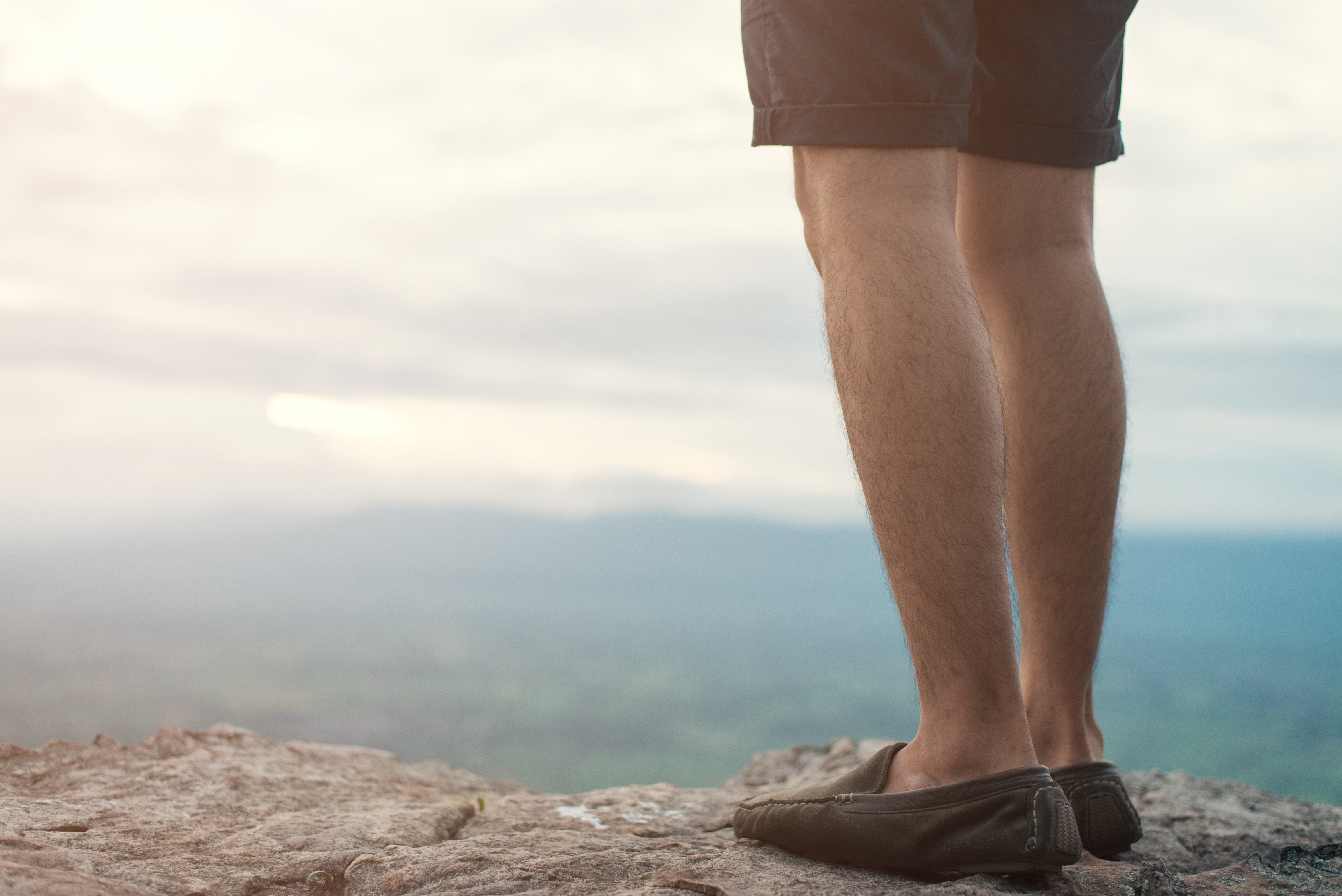 Man standing on a cliff looking off into the distance.
