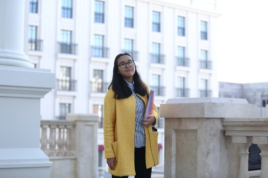 Woman in Yellow Coat Standing Holding Book during Daytime
