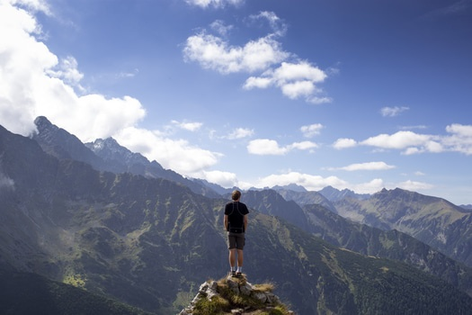 Man in Black Shirt and Gray Shorts Standing on Cliff Under White and Blue Cloudy Sky