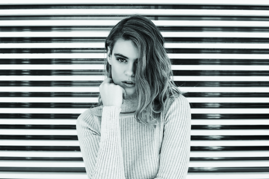 Grayscale Photo of Woman in Turtle Neck Shirt Standing in Front of Window Blinds