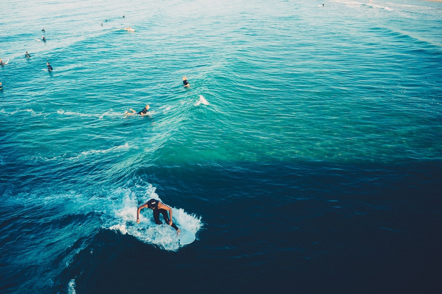 Picture of people waiting for the wave with one person in the middle of catching the wave.