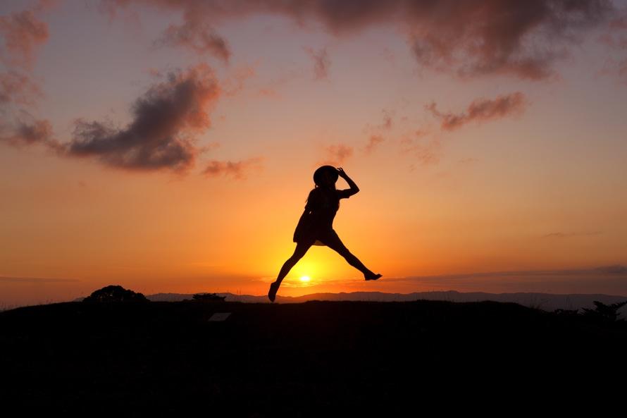 Salto de la persona durante la puesta del sol en la Vista de ángulo bajo Fotografía