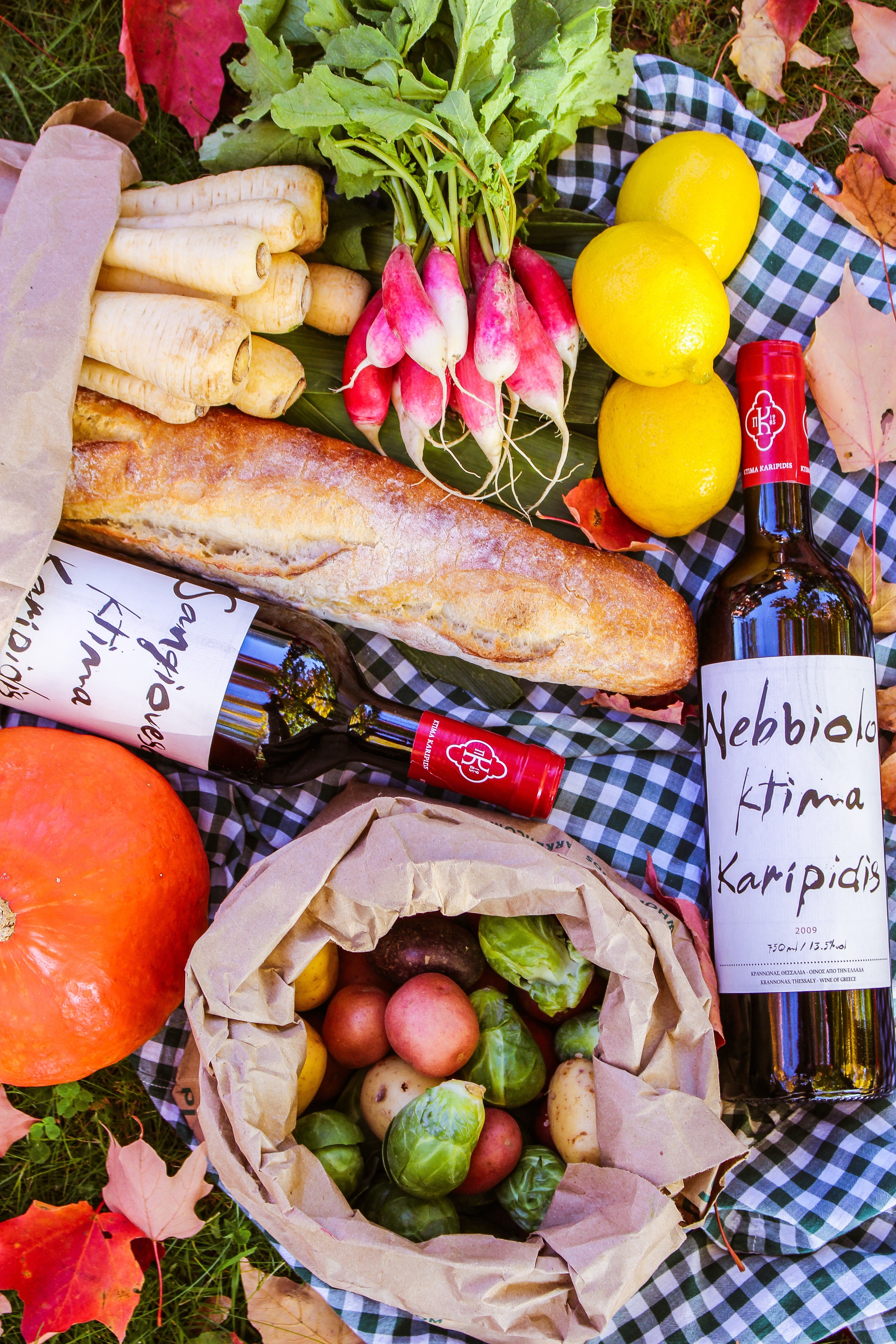 Fruit, vegetables, bread and wine laid out on a picnic blanket