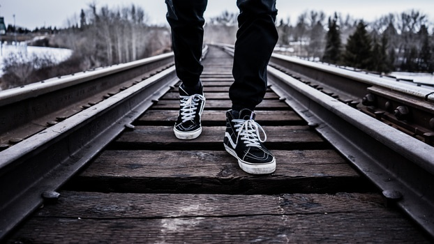 Person in Black Pants With Black Vans High Top Sneakers Standing on Railroad Tracks during Daytime
