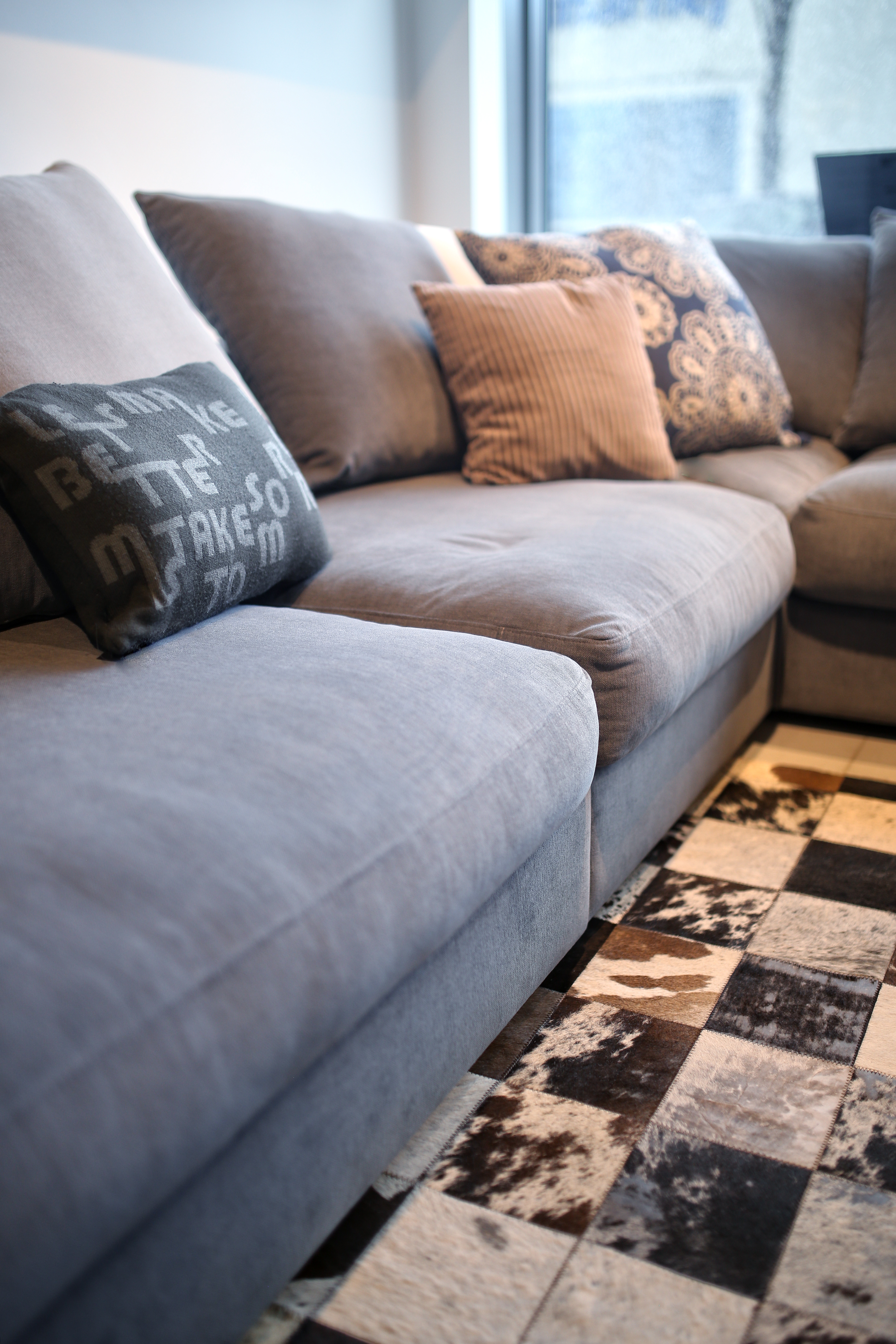 Comfortable grey couch with pillows ? Free Stock Photo