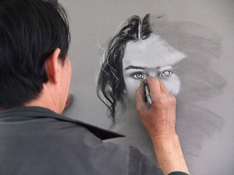 Person in Black Jacket Drawing Woman's Face on Wall