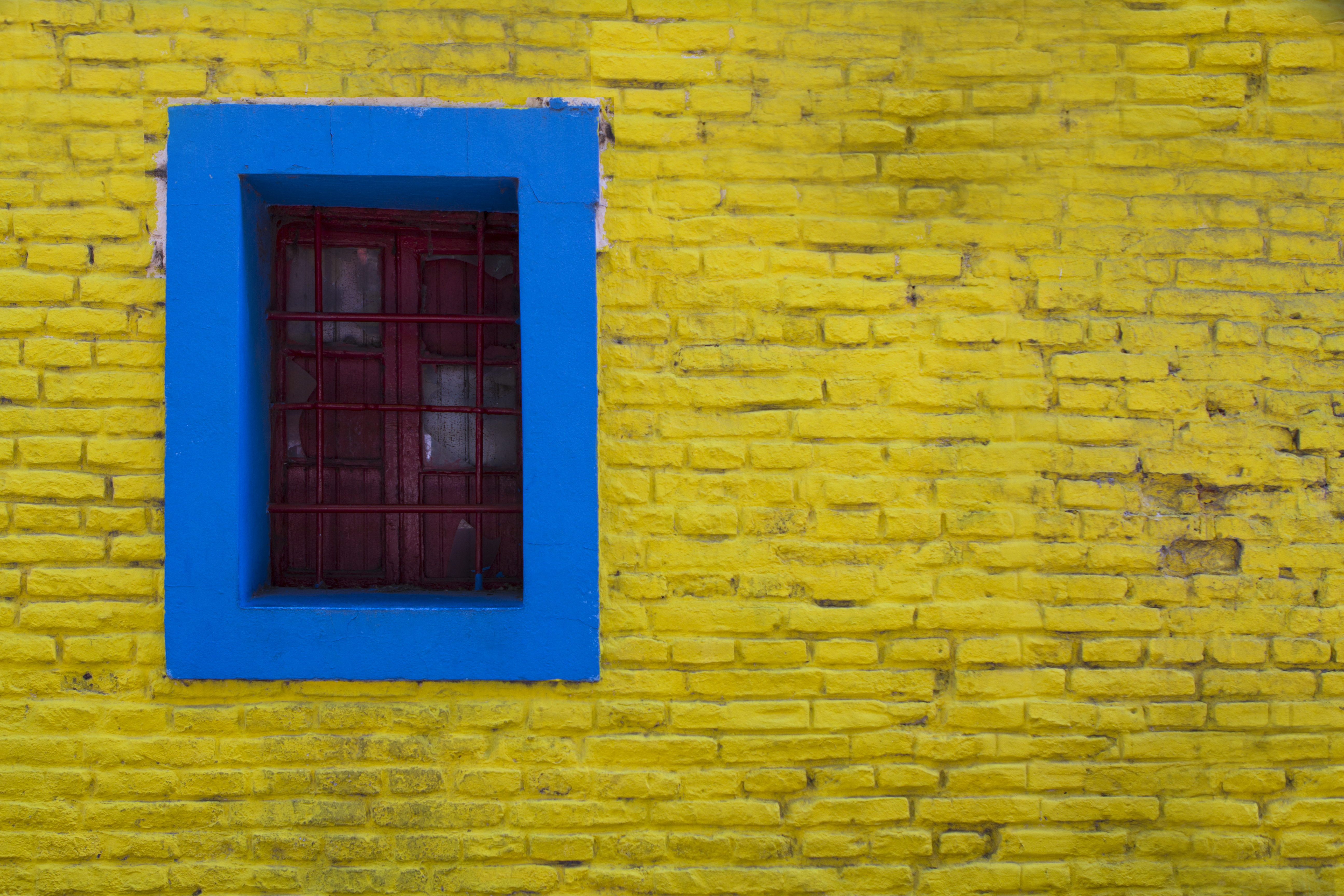 painted stone wallBlue Trim Around Window in Yellow Painted Stone Wall  Free Stock