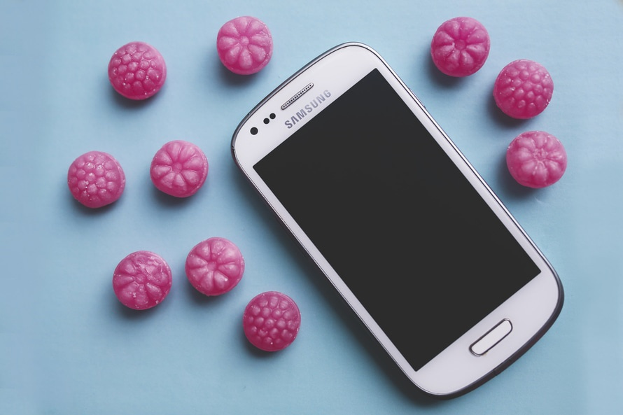 Pink candies and white smartphone