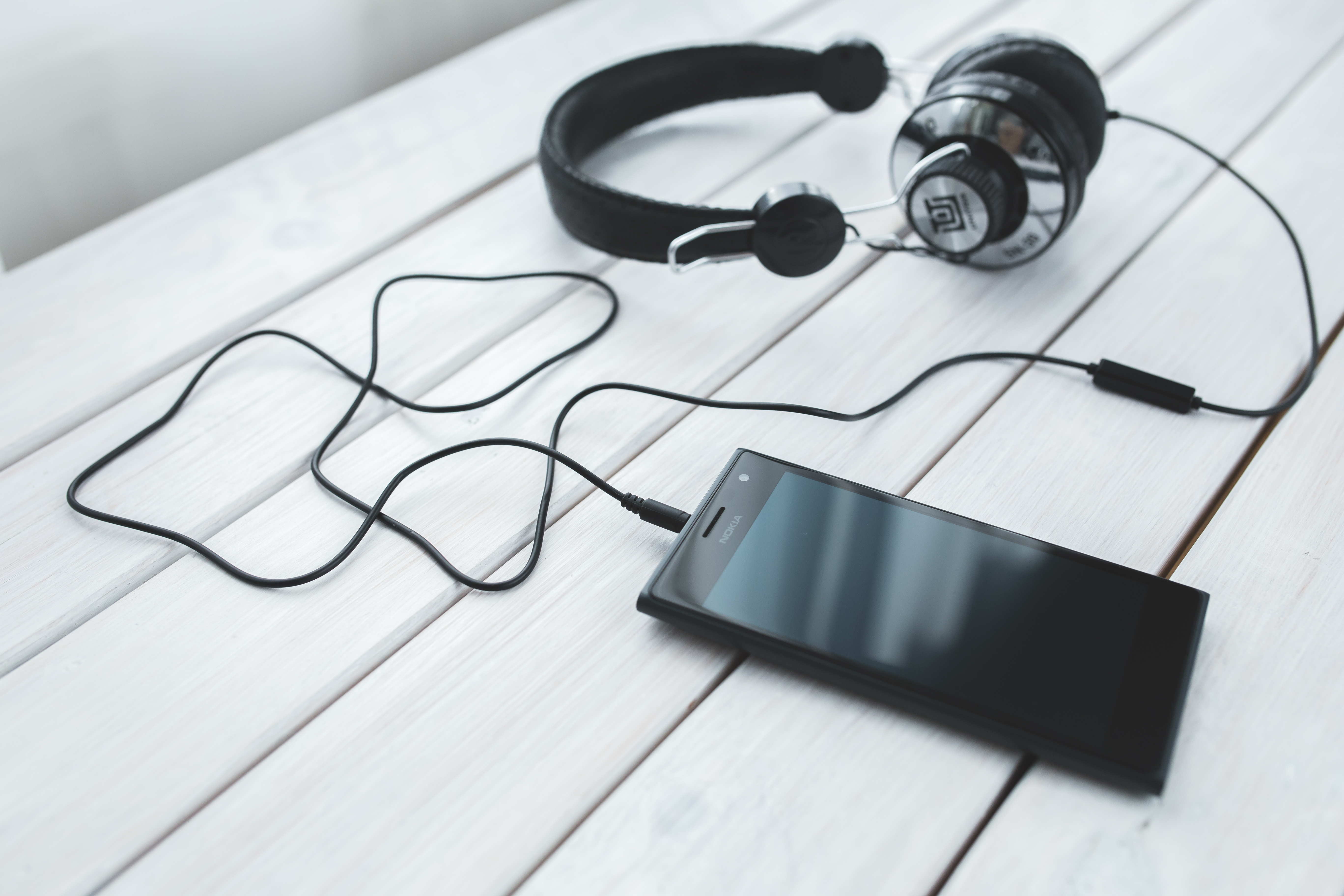Black smartphone and headphones on a desk · Free Stock Photo