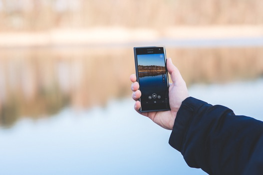 Man taking photo of a lake with mobile phone