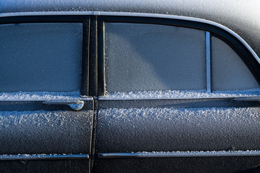 Black Sedan With Snow on the Side of the Window