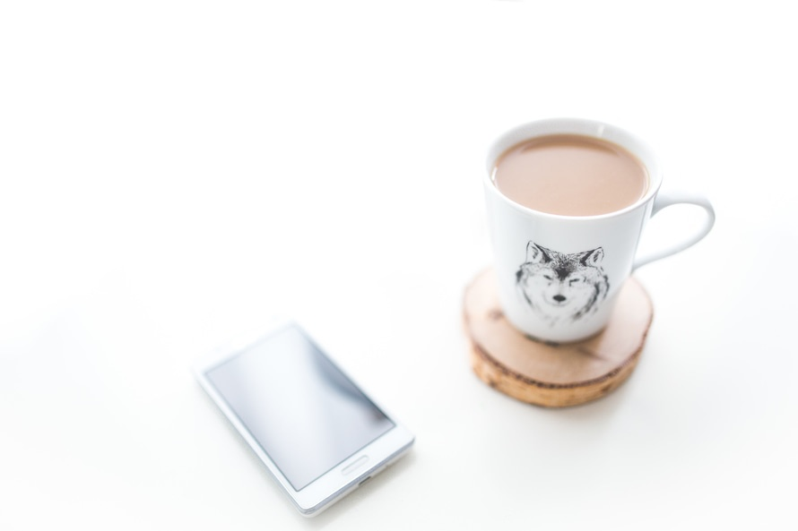 White desk with a cup of coffee and mobile phone