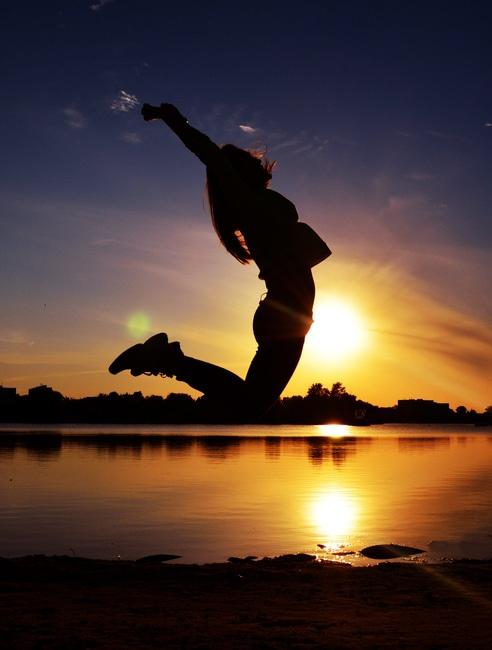 Mujer de salto Cerca Cuerpo de agua