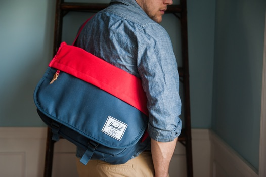 Man in Blue Chambray Long Sleeve Shirt With Red and Blue Herschel Sling Bag