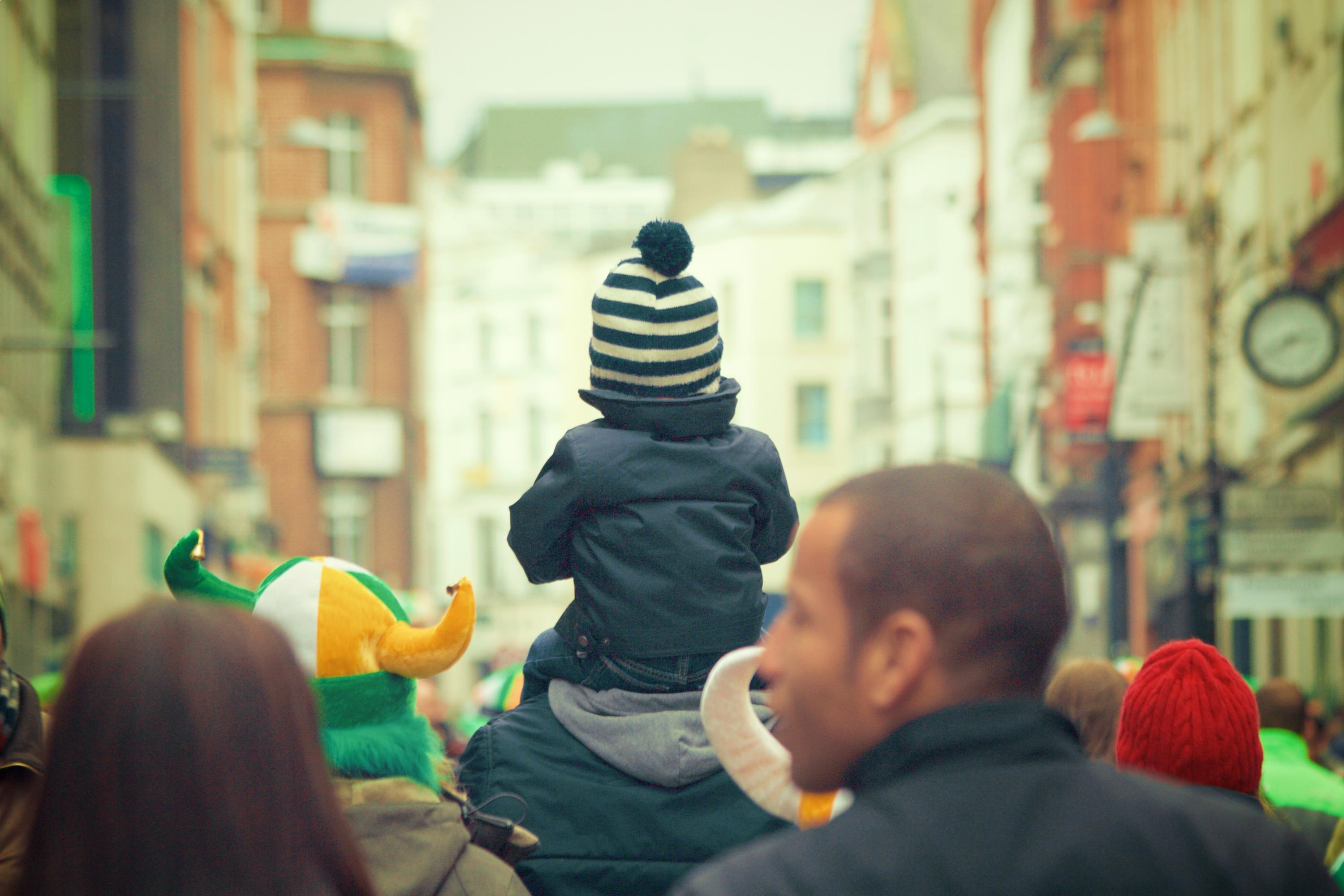 Image of toddler in Fall jacket and toque on top of parent's shoulders facing away from camera.
