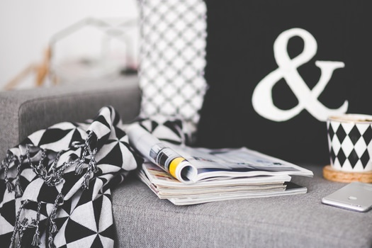 Close of magazines, mug and phone on a couch