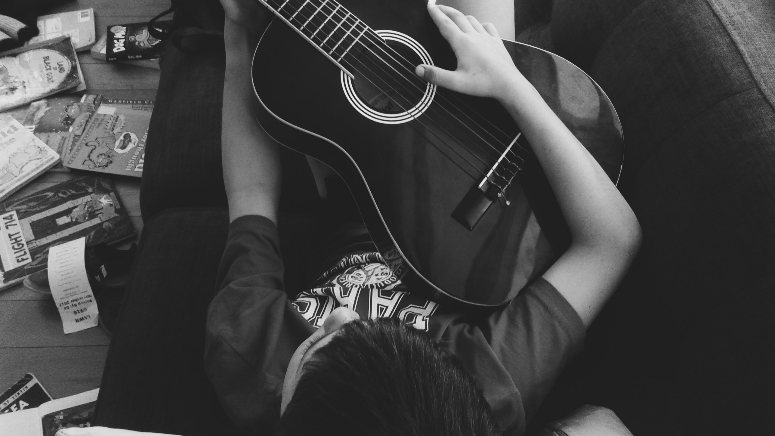 Man Playing Guitar Lying On Couch In Grayscale Photography Free Stock Photo