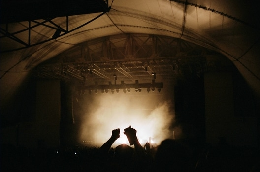 This photo shows a concert venue inside a huge tent. A crowd is gathering in front of the stage cheering. The stage itself is covered in fog and light. The photo has sepia colors.