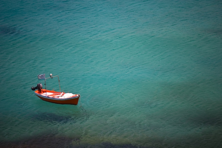 sea, red boat with Greece flag: secluded trip.