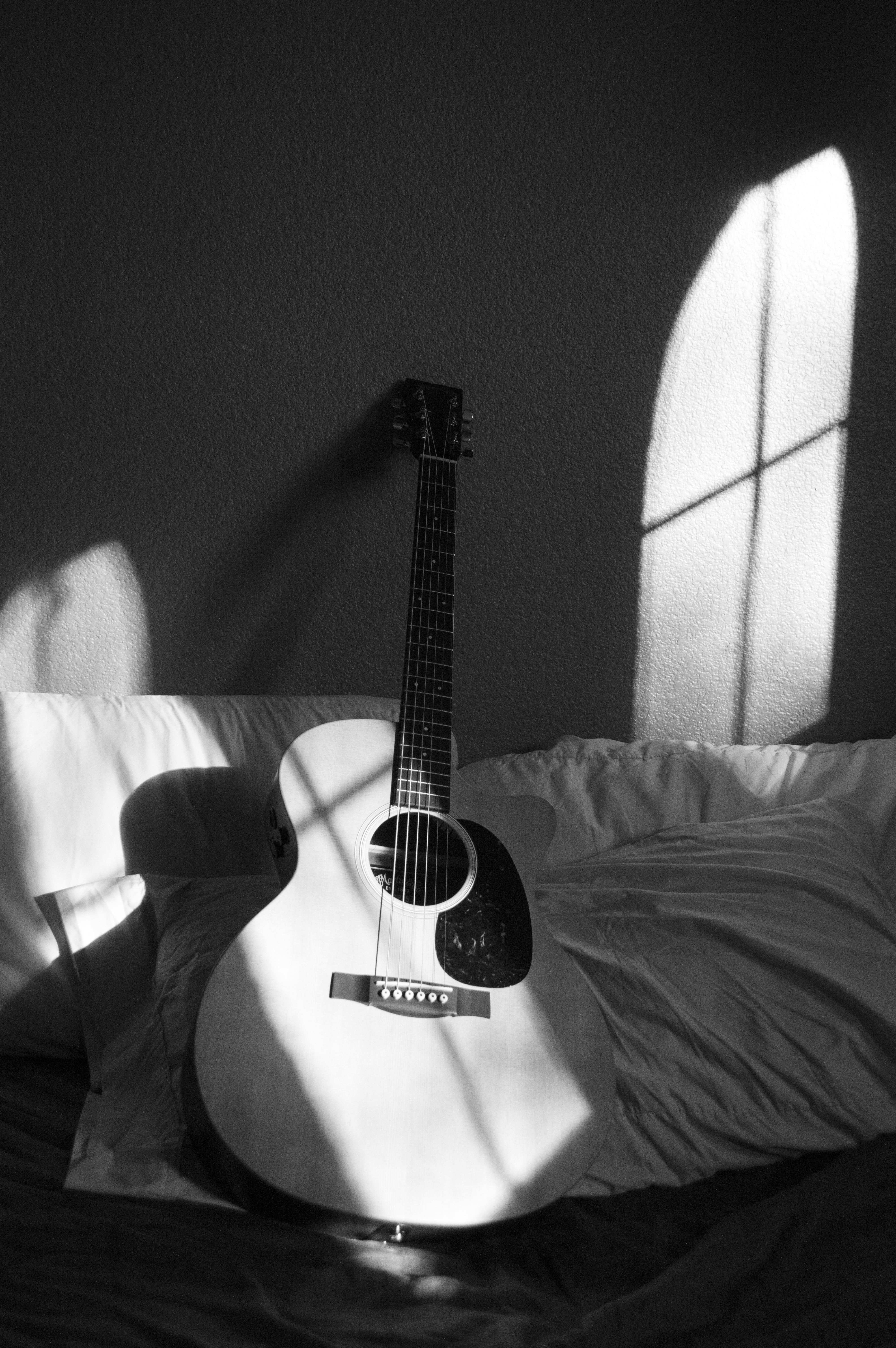 white acoustic guitar on grey and white textile  free stock photo