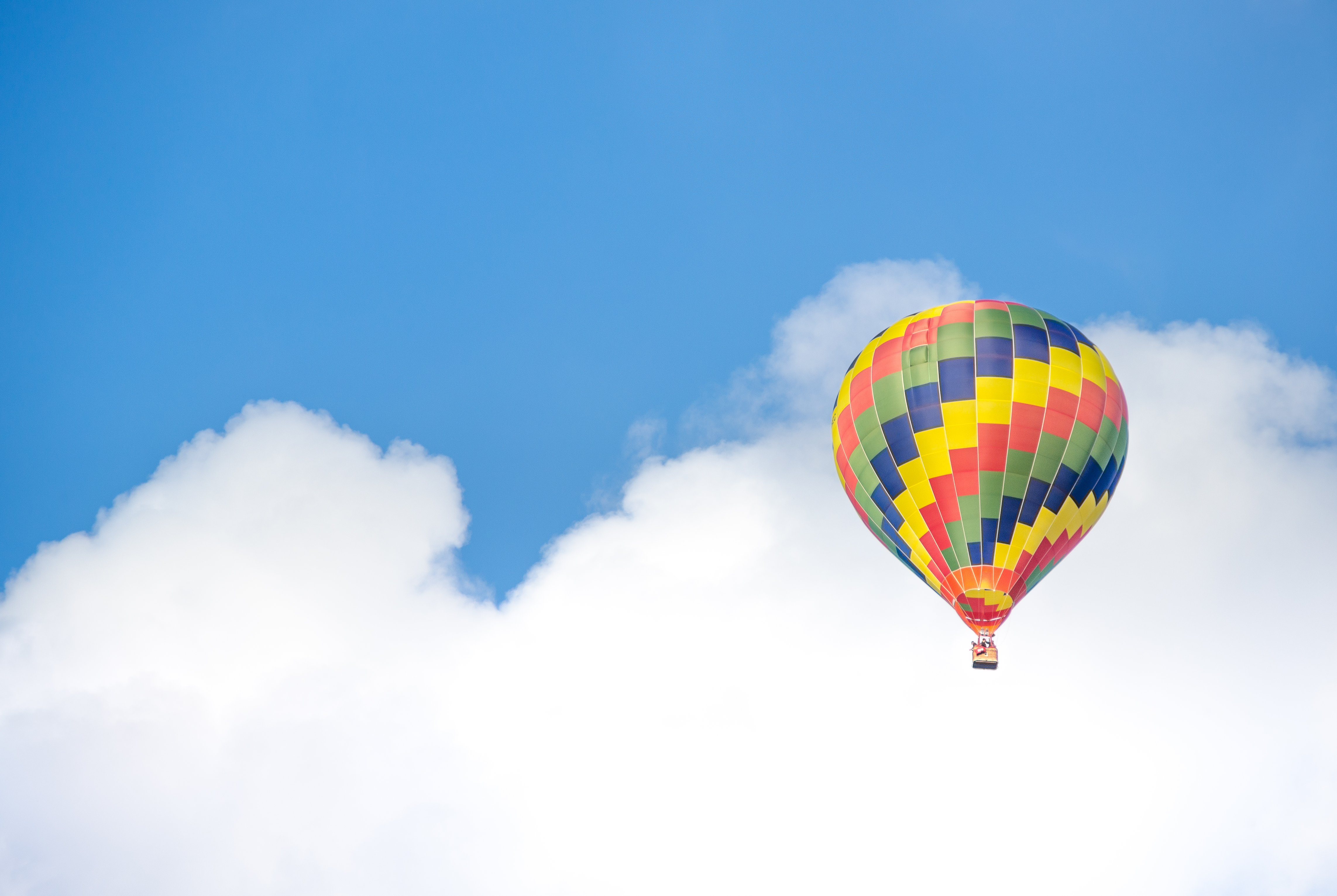 yellow blue and green air balloon flying near white clouds