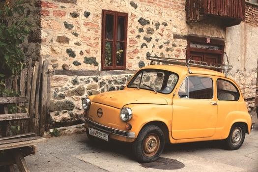 Yellow Nissan Classic Car Beside Gray Beige Concrete Building