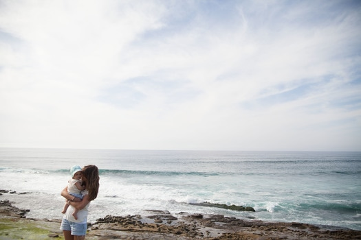 Mother Holding Her Baby in Front of Seashore during Daytime