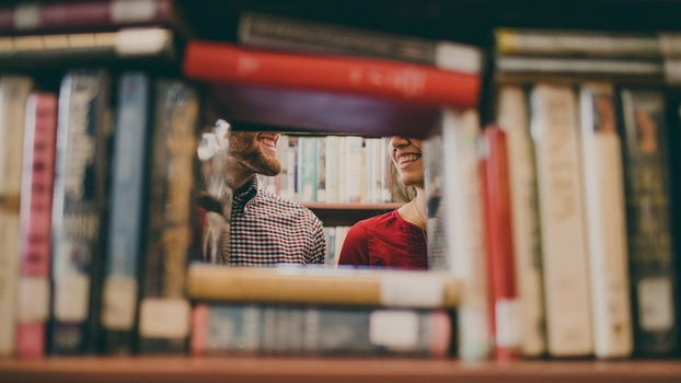 Couple Smiling Behind Books