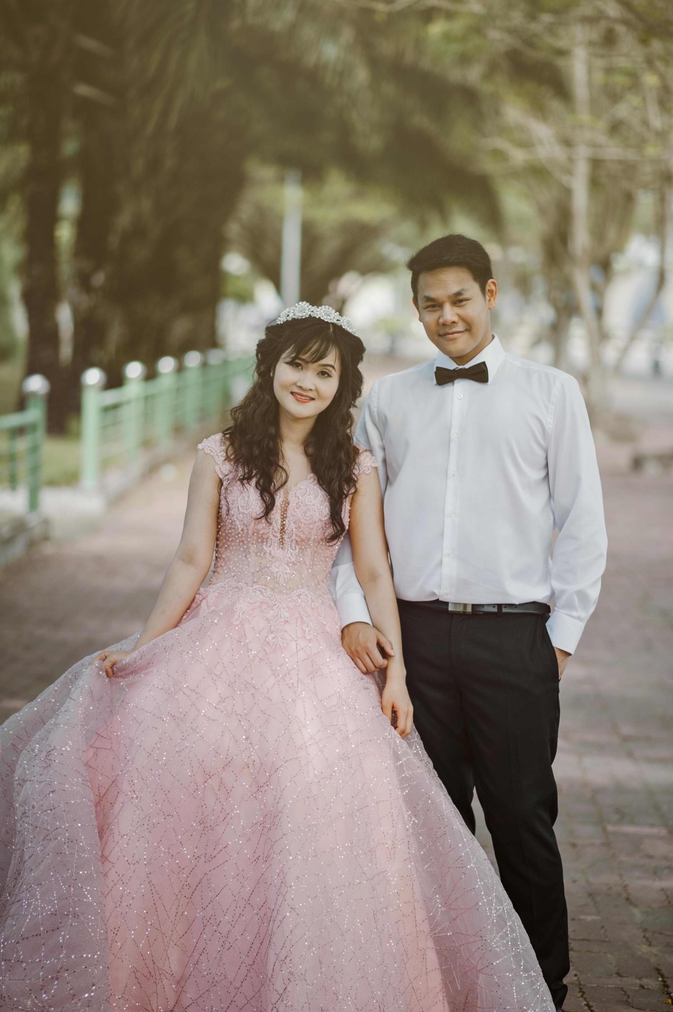 Woman wearing pink wedding gown standing next to man wearing white free download junglespirit Image collections