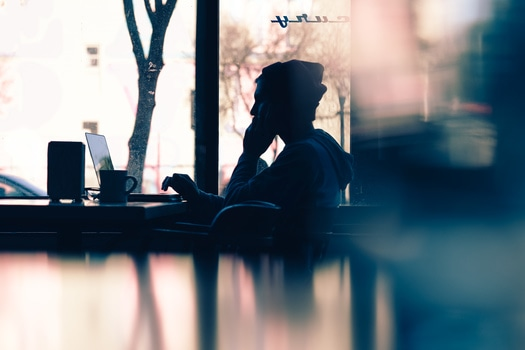 Silhouette of Man in Front of Laptop Near Window during Daytime