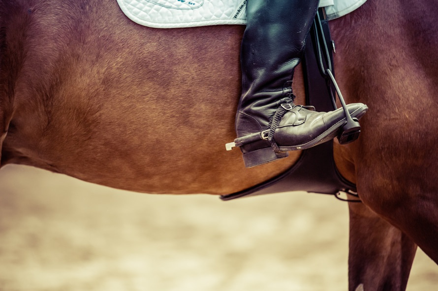 Person Riding Brown Horse Put His Feet on Horse Saddle