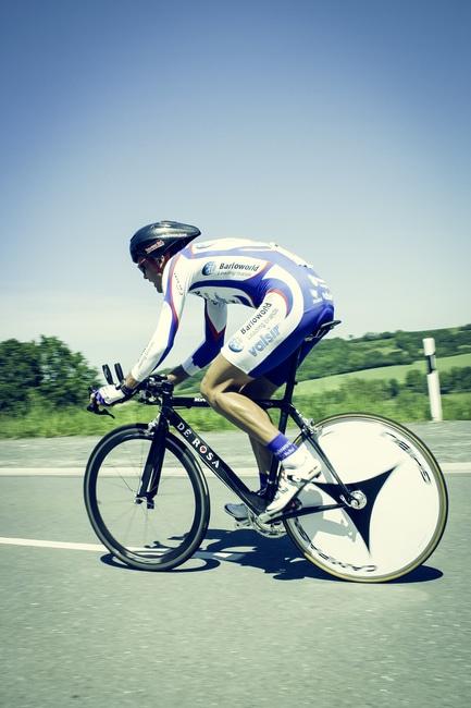 Cycliste sur Gris Asphalt Road Under Blue Sky au cours de la journée