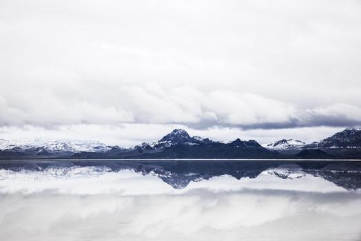 Black Snowy Mountain Near Body of Water Under Blue Sky